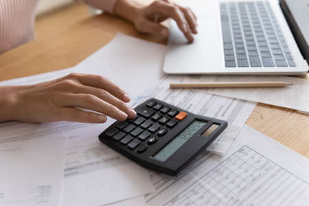 Accounting is an exact science. Close up cropped view of young woman enterpreneur hands doing financial paperwork check money savings sum on bank account calculating goods service price paying bills