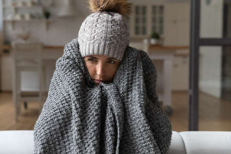 Dull young hispanic woman save herself from freezing wear winter clothes muffle up in blanket think of buying radiator heater. Shivering young lady sit on sofa in plaid ponder on much too cold at home