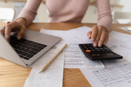 Bookkeeping requires accuracy. Young woman hands typing on computer and digital calculator keyboards preparing electronic payments of utility bills counting taxes sum balancing accounts. Close up view