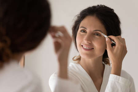 Close up smiling woman in white bathrobe plucking thick eyebrows with tweezers, looking in mirror, attractive young female correcting shape, beauty procedure and make up, standing in bathroom Foto de archivo