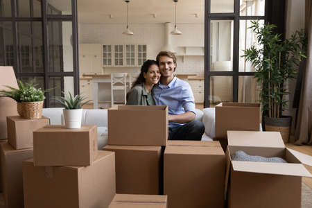 Portrait happy family sitting on couch with cardboard boxes, relocation and moving day concept, smiling wife and husband looking at camera, preparing to relocation, mortgage or rent concept
