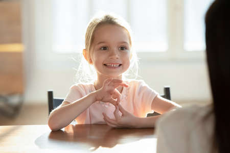 Cute little Caucasian girl child speak talk engaged in educational activity with mom or nanny at home. Small kid study distant learn pronouncing sounds with teacher or tutor. Education concept.