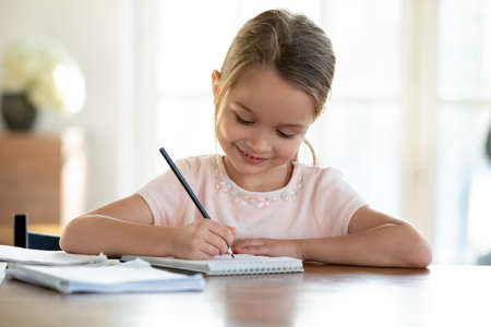 Cute smart little 7s girl child sit at table at home write in exercise book prepare homework alone. Happy small kid do task assignment, handwrite in notebook, study for school. Education concept. Фото со стока