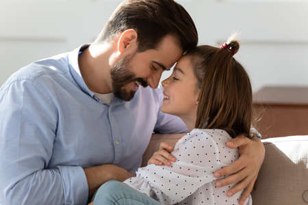 Caring young Caucasian father and little teenage daughter hug cuddle enjoy close intimate family moment at home together. Loving happy dad parent and teen girl child embrace share secrets.