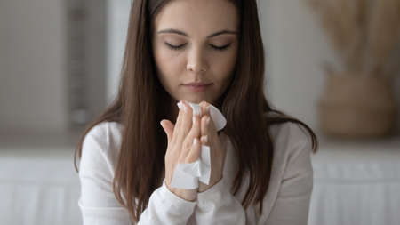 Sad student girl suffering from running nose, seasonal allergy, flu or cold, staying at home, feeling bad, holding tissue, handkerchief at face. Woman having respiratory infection, sneezing, coughing