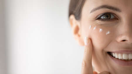 Happy young woman putting moisturizing nourishing cream, cleansing lotion on smiling face, applying cosmetics for keeping healthy fresh skin. Cosmetology, skincare concept, Close up, cropped portrait Stock Photo
