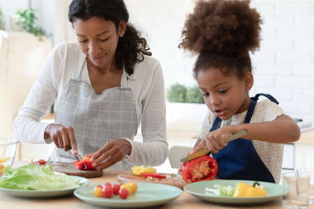Happy mommy and cute daughter girl in aprons cooking together in kitchen. Mom and kid slicing fresh vegetables for salad, preparing healthy organic meal and talking. Family eating at home concept