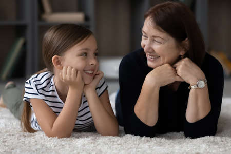 Smiling mature 60s Caucasian grandmother and cute little teenage granddaughter relax lie on carpet in living room. Happy loving elderly granny and small teen girl child have fun rest together at home.