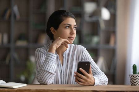 Dreamy Indian businesswoman distracted from phone, looking to aside, sitting at work desk with smartphone, planning day, dreaming about good future, visualizing new opportunities, waiting for call 版權商用圖片