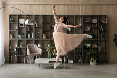 Overjoyed Indian woman wearing dress dancing, jumping in modern living room interior alone, having fun, listening to favorite good music, happy beautiful young female enjoying leisure time at home