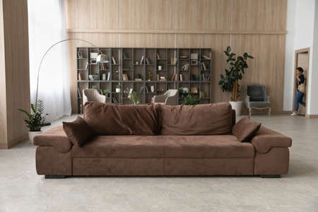 Indian woman returning home, opening door, young female student or businesswoman with backpack entering into empty modern living room after workday on background, cozy brown sofa standing in apartment 版權商用圖片