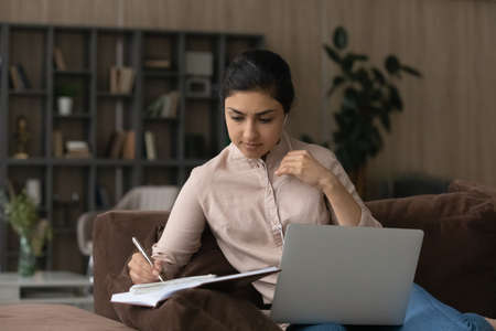 Close up focused Indian woman in earphones taking notes, studying online, motivated confident young female student listening to lecture or watching webinar at home, using laptop, sitting on couch