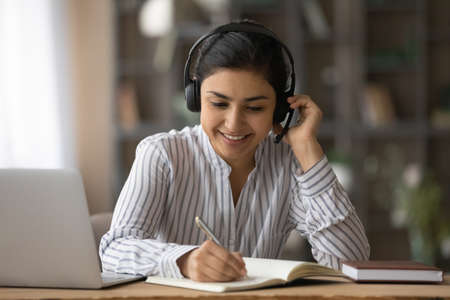 Close up smiling Indian woman in headphones writing taking notes, studying online, sitting at desk with laptop, listening to online lecture, course, watching webinar, student preparing to exam