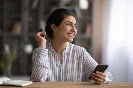 Smiling dreamy Indian woman holding credit card and smartphone, sitting at desk, looking to aside, happy young female shopping and paying online at home, satisfied customer using internet banking 版權商用圖片