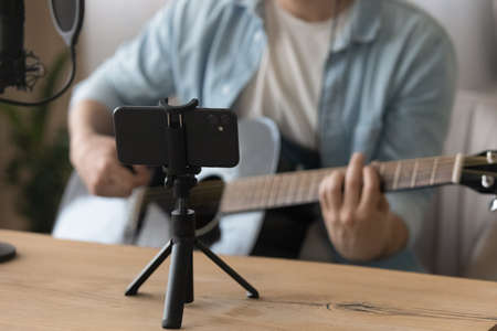 Close up smartphone on tripod, cropped of man playing guitar, musician artist recording new song video for social network, blogger or music teacher shooting course in home studio, sitting at desk 版權商用圖片