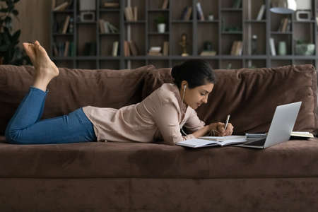 Side view Indian woman in earphones lying on couch, studying online, young female student listening to lecture, watching webinar, involved in internet lesson, writing taking notes, remote education