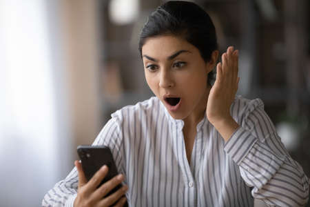 Close up shocked Indian woman with open mouth looking at smartphone screen, reading unexpected unbelievable news in message, surprised businesswoman money refund or job promotion, online lottery win