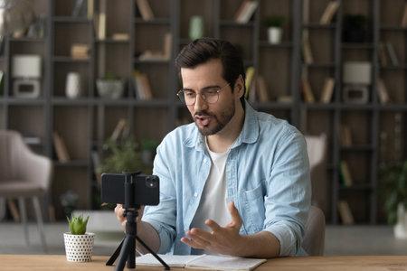 Young man blogger in glasses recording video, speaking, using smartphone standing on tripod, sitting at work wooden desk, confident teacher shooting webinar or leading online lesson, explaining 版權商用圖片