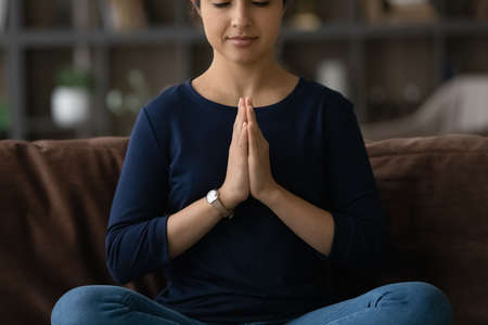 Close up peaceful Indian woman meditating, calm mindful tranquil young female sitting in lotus pose on couch at home alone, dreaming and visualizing, doing yoga exercise, stress relief concept