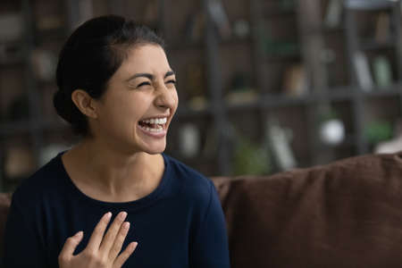 Close up overjoyed Indian woman laughing, sitting on couch, excited happy young female with healthy toothy smile looking in distance, having fun, watching comedy movie on tv or funny video