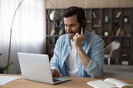 Smiling businessman talking on smartphone, using laptop, sitting at desk, friendly manager freelancer consulting customer by phone call, negotiating, looking at computer screen, searching information