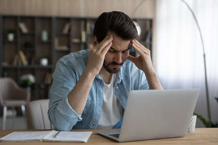 Upset businessman with closed eyes touching massaging temples, suffering from strong headache or chronic migraine at workplace, sitting at desk with laptop, tired exhausted young man feeling pain