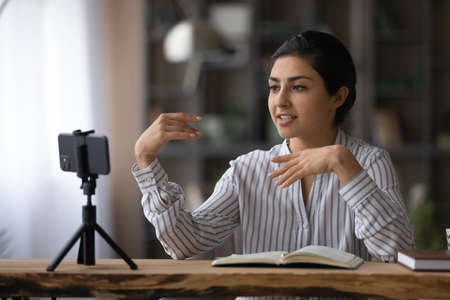 Smiling Indian woman coach speaking, leading online lesson, training course, broadcast or recording webinar on smartphone standing on tripod, popular blogger shooting video for social network