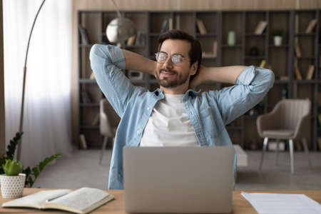 Positive dreamy businessman in glasses sitting at desk with laptop, leaning back, stretching hands, relaxing after work finished and daydreaming about good future, new career opportunities 版權商用圖片