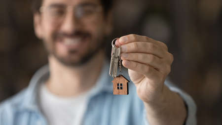 Close up focus on keys, satisfied man excited by relocation, smiling tenant renter moving into new house, overjoyed customer purchasing first own apartment, real estate, mortgage or rent 版權商用圖片