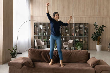 Happy overjoyed Indian woman jumping on couch at home, celebrating success, excited by relocation in new apartment, smiling young female dancing in living room, funny activity, having fun alone 版權商用圖片