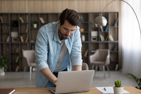 Confident businessman in glasses working on laptop, typing, standing at home office desk, serious focused young man looking at screen, freelancer reading or writing business email, research project