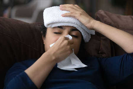 Close up sick Indian woman blowing nose, sitting on couch at home, exhausted young female with towel on head feeling unhealthy and unwell, suffering from high temperature, catch cold or flu