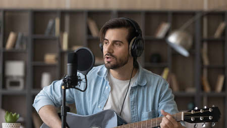 Close up man in headphones playing guitar, singing in microphone, popular musician artist recording new song or podcast in home studio, composing, using musical instrument, hobby and music concept