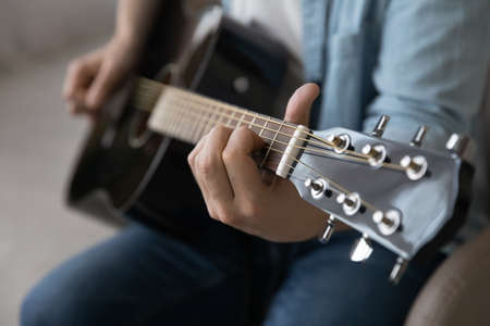 Close up man playing acoustic guitar, talented artist musician making music, songwriting, working on new song, using musical instrument, student practicing at lesson, hobby passion concept 版權商用圖片
