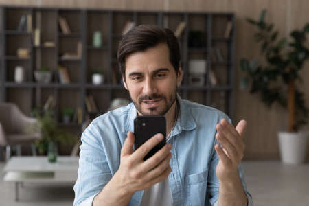 Confident businessman making video call, involved in internet conference with business partners, holding smartphone, looking at screen and talking, young male chatting online with friend or relatives