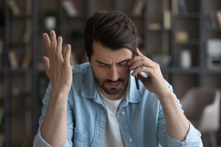 Close up unhappy businessman talking on smartphone, hearing bad news, unexpected debt or bankruptcy, financial problems, dismissal notification, frustrated upset young man making phone call