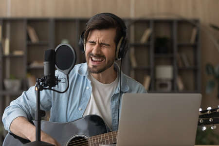 Close up man wearing headphones singing in professional microphone, playing guitar, musician artist recording new song, making music in home studio, using laptop, teacher holding online lesson