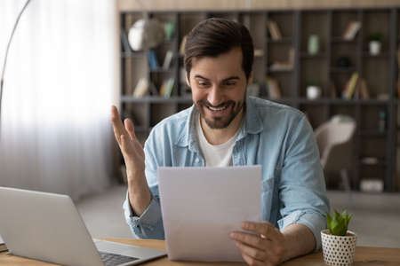 Excited businessman reading good news in letter, notification, sitting at workplace with laptop, overjoyed young man holding documents, received money refund or job promotion, celebrating success