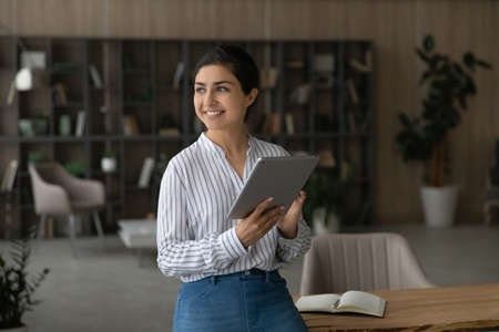 Dreamy smiling Indian businesswoman holding tablet, looking to aside, standing in home office, happy young female visualizing future, dreaming about new job opportunities, distracted from work 版權商用圖片