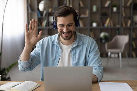 Smiling man in headphones and glasses waving hand at webcam, using laptop, chatting, making video call to relatives or friends, teacher greeting students, businessman involved in internet meeting 版權商用圖片