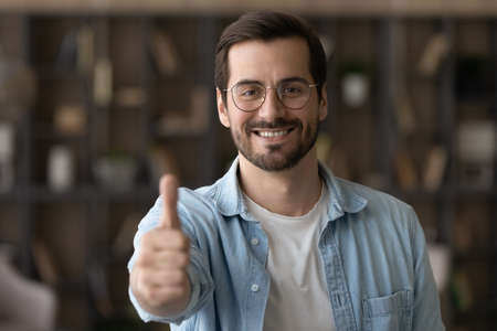 Head shot portrait smiling young man in glasses showing thumb up at camera, happy customer client recommending good quality service, feeling satisfied and excited, feedback and review concept