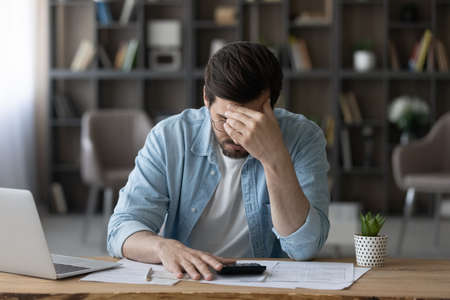 Unhappy businessman in glasses calculating bills, worried by financial problem, unexpected debt, bankruptcy, frustrated young man sitting at desk with laptop and calculator, lack of money concept