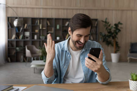 Overjoyed surprised man reading good news in message, looking at smartphone screen, sitting at desk, excited by success, happy young male received money refund or job promotion, online lottery win