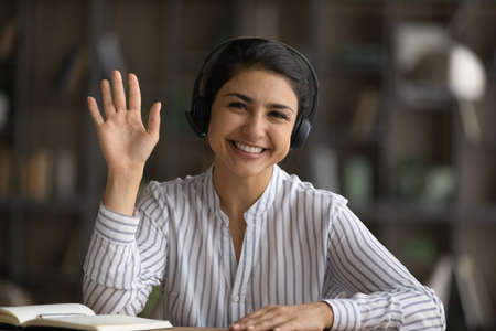 Head shot portrait smiling Indian woman in headphones waving hand and looking at camera, happy businesswoman involved in internet meeting, video call, greeting viewers, teacher leading online lesson 版權商用圖片