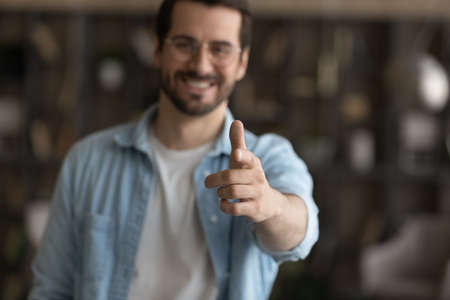 Close up smiling man in glasses pointing finger at camera, blurred background, excited friendly hr manager employer leader choosing you as candidate in team, recruitment and employment concept 版權商用圖片