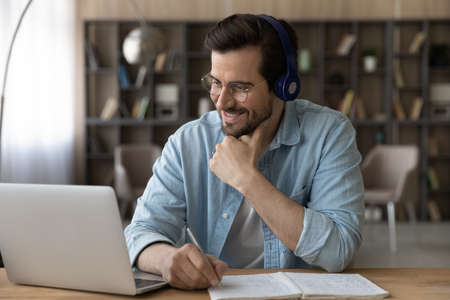 Close up smiling man in headphones and glasses using laptop, writing taking notes, motivated student watching webinar or training, listening to lecture, learning language, studying online at home