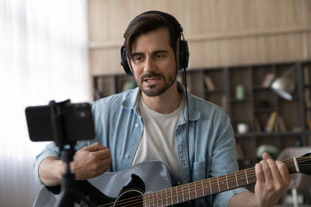 Close up man in headphones playing guitar and singing, recording on smartphone, musician artist recording new song video for social network, blogger or music teacher shooting course in home studio 版權商用圖片