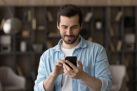 Close up satisfied man using phone, looking at screen, standing at home, positive young male holding smartphone, chatting in social network with friends or shopping online, enjoying leisure time