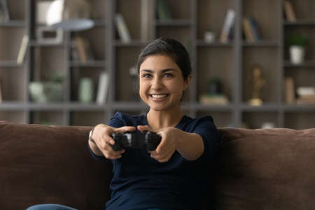 Close up smiling Indian woman playing video game on tv, holding controller, sitting on couch at home alone, excited interested young female enjoying leisure time, involved in funny virtual app 版權商用圖片