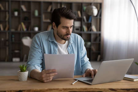 Focused businessman using laptop, looking at screen, serious man working with financial documents or correspondence, checking data, analyzing statistics, student busy with research project 版權商用圖片
